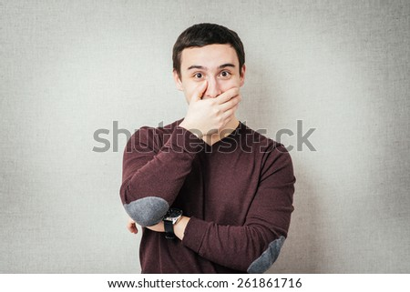 man covers his mouth so as not to laugh