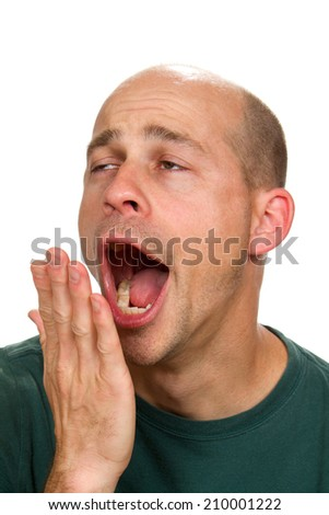 Man covers his mouth with his hand as he yawns with a funny expression. - stock photo