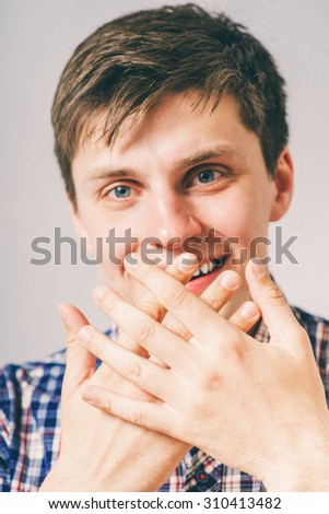 man covers his mouth with his hands and holding back laughter - stock photo
