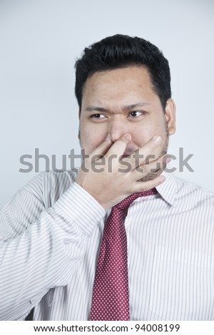 Man covers nose due to bad smell - stock photo