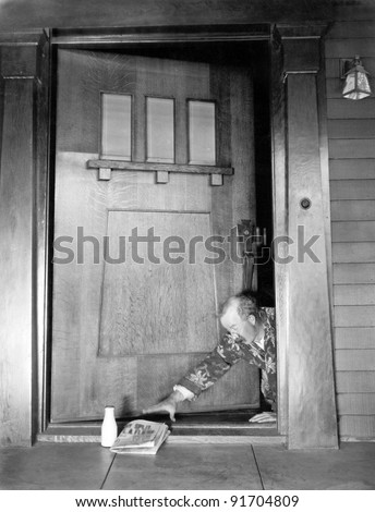 Man crawling at the front door  to reach his newspaper and milk - stock photo