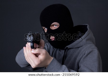 man criminal in black mask aiming with gun over grey background - stock photo