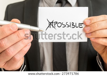 Man crossing through the Im in the handwritten word Impossible on a white business card with a metallic fountain pen in a concept of opposites for Impossible - Possible. - stock photo