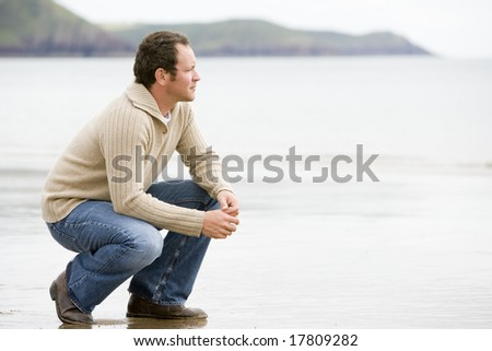 Man crouching on beach - stock photo