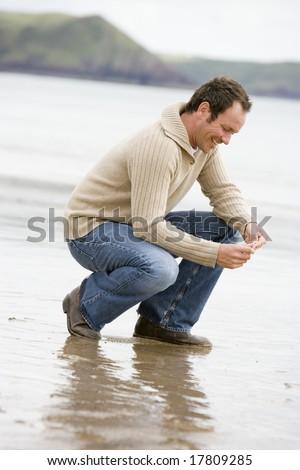 Man crouching on beach - stock photo