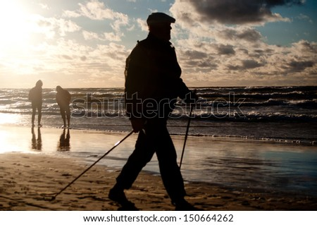 Man cultivating Nordic Walking on the beach - stock photo