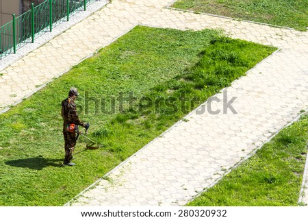 man cuts the grass in the yard trimmer - stock photo