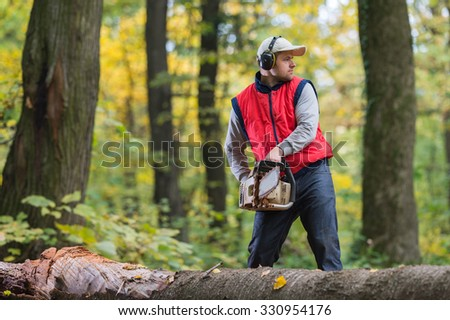 Man cutting a branch with chainsaw