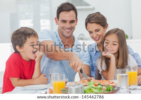 Man cutting a pizza for his family for the dinner - stock photo