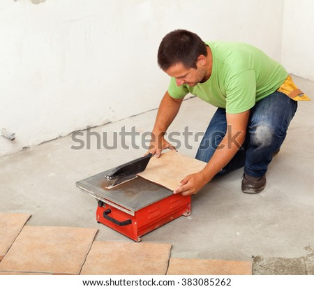 Man cutting ceramic floor tile - kneeling by a cutter machine