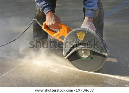 Man cutting control groove in concrete slab - stock photo