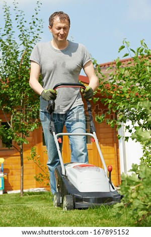 man cutting grass in his garden yard with lawn mower - stock photo