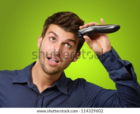 Man Cutting His Hair With Razor On Green Background - stock photo