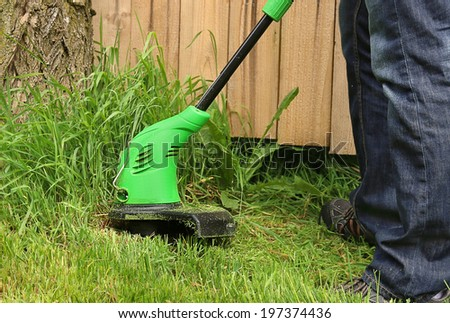 Man cutting the grass with electric trimmer - stock photo