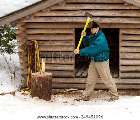 Man cutting wood with an axe. - stock photo