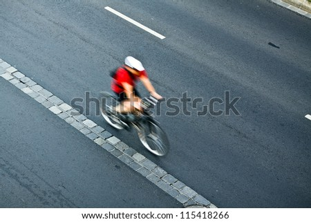 Man cycling on city street, motion blur, commuting cyclist - stock photo