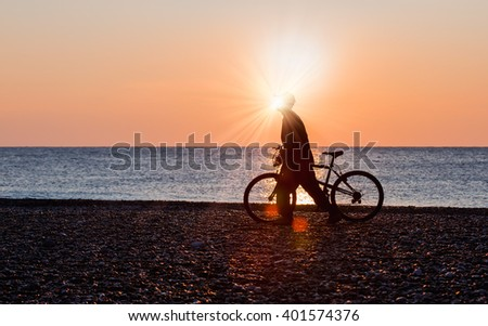 man cyclist silhouette on golden sky and sunset background on the beach - stock photo