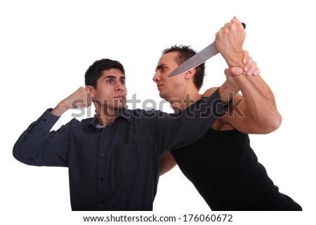 Man defending himself against a knife attack isolated on white - stock photo