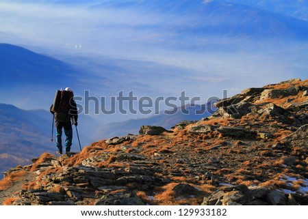 Man descending a mountain trail in autumn - stock photo