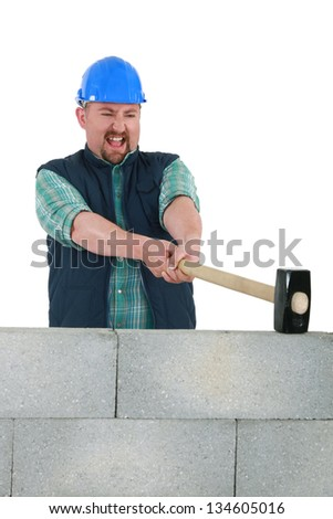 Man destroying wall with sledge-hammer - stock photo