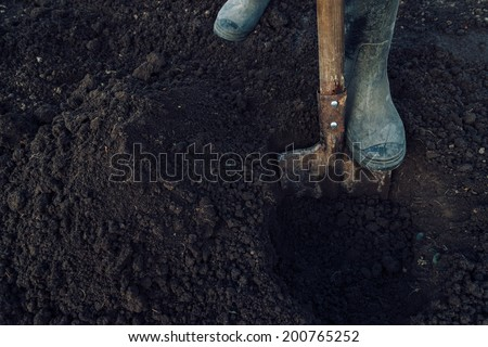Man digs a hole by shovel in garden, face is not visible, agriculture - stock photo