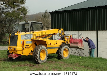 Man directing the tipping of gravel from a telescopic loader.