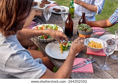 man dishing healthy fresh salad at outdoor barbecue garden party gathering - stock photo