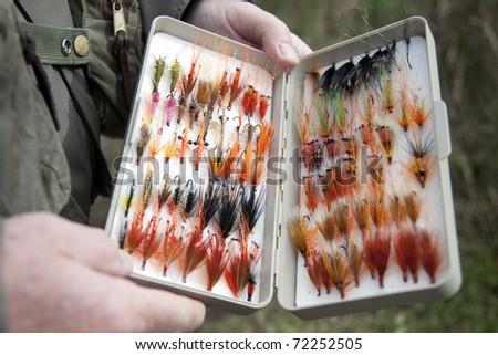 Man displays his fishing flies - stock photo