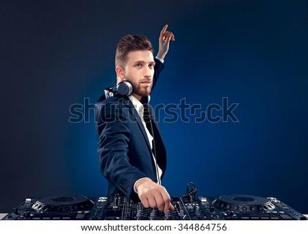 Man DJ in dark suit play music on a Dj's mixer. Studio shot. Dark blue background - stock photo