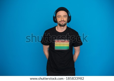 man dj wearing headphones on blue enjoying the music - stock photo