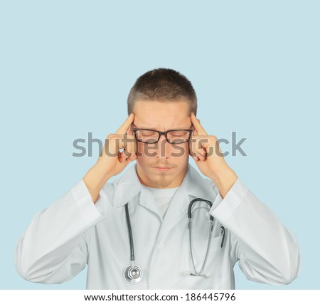 Man doctor with migraine headache overworked, doctor touches his head - stock photo