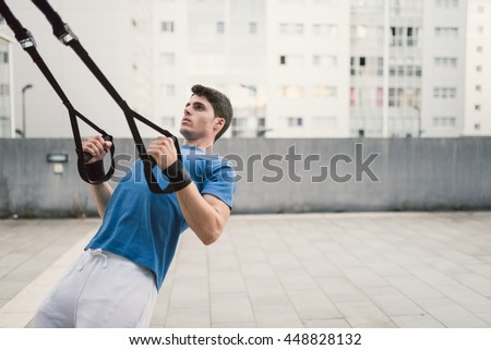 Man does crossfit push ups with trx fitness straps in the street - stock photo