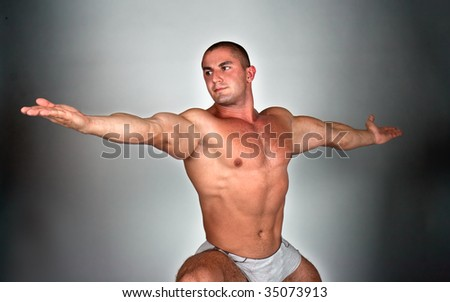 Man doing a virabhadrasana (variant), studio shot - stock photo