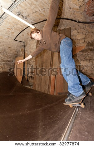 Man doing an axle stall in a skateboard pipe - stock photo