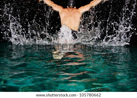Man doing butterfly strokes while swimming in a pool at night, creating a curtain of water and droplets.