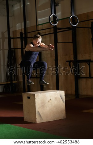 Man doing cross-training exercise. He jumping on wooden box. - stock photo