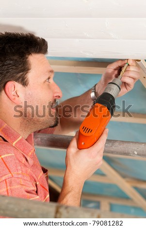 Man doing dry walling, working under a roof slope - stock photo