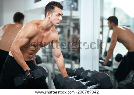 man doing exercises dumbbell bicep muscles in the gym