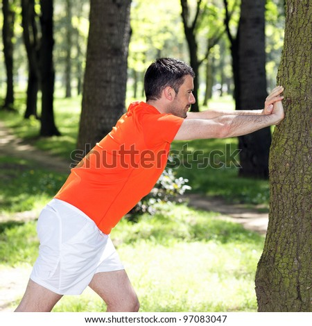 man doing exercises in a park in summer - stock photo