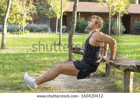 Man doing exercises in the park. - stock photo