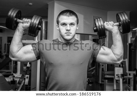 Man doing exercises with dumbbell in the gym