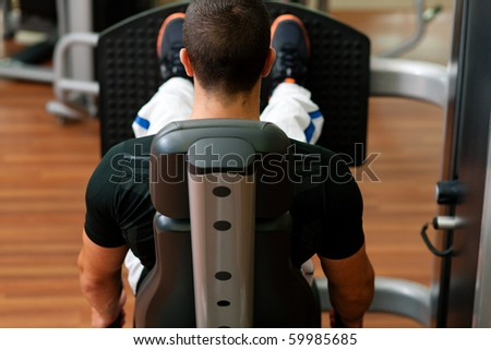 Man doing fitness training on leg press with weights in a gym - stock photo