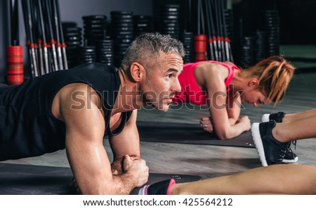 Man doing push ups in fitness class - stock photo