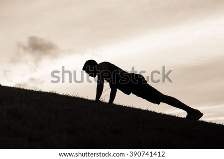 Man doing push ups in the park.  - stock photo