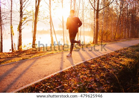 Man doing running exercise at autumn, winter morning