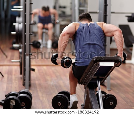 Man doing shoulders and back workout in front of the mirror in the gym - stock photo