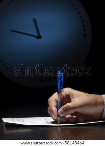 man doing written test with the clock in the background, low key, useful for job application.education and other testing related themes - stock photo