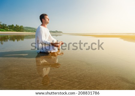 Man doing yoga asana meditating in a lotus position - stock photo