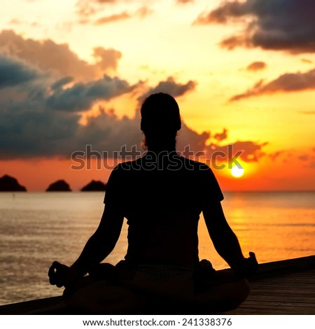 man doing yoga at sunset - stock photo