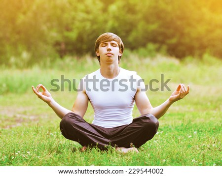 Man doing yoga exercises outdoors on the grass  - stock photo